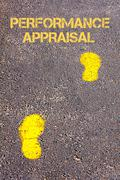Yellow footsteps on sidewalk towards Performance Appraisal message - stock photo