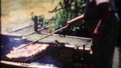 1801 - chef barbecues lamb over the grill on summer day -vintage film home movie Stock Footage