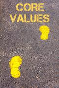 Yellow footsteps on sidewalk towards Core Values.Ethics Conceptual image Stock Photos