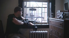 Man aiming gun out window Stock Footage