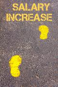 Yellow footsteps on sidewalk towards Salary Increase message.Conceptual image Stock Photos
