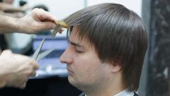 Barber cuts male hair bangs with scissors - stock footage