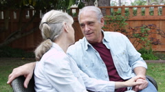 Elderly couple sitting talking in yard at home Stock Footage