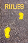 Yellow footsteps on sidewalk towards Rules message.Conceptual image Stock Photos