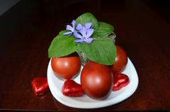 Colored eggs on white saucer with violet flowers. - stock photo