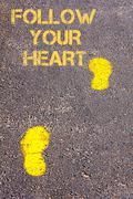 Stock Photo of Yellow footsteps on sidewalk towards Follow your heart message.Conceptual ima