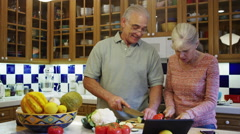 Senior couple having fun cooking together in kitchen - stock footage