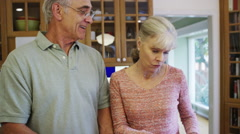 Happy senior couple using tablet and cooking in kitchen - stock footage
