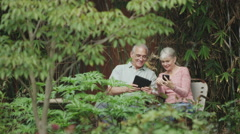 Happy senior couple using tablet smartphone outside in yard Stock Footage