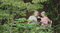 Happy senior couple using tablet smartphone outdoors Stock Footage