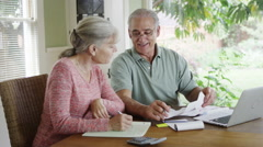 Senior couple paying bills together on laptop - stock footage