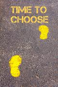 Yellow footsteps on sidewalk towards Time to Choose message.Conceptual image Stock Photos
