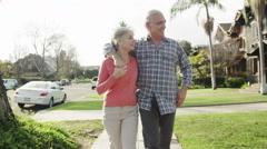 Sweet senior couple walking through neighborhood Arkistovideo