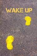 .Yellow footsteps on sidewalk towards Wake Up message.Conceptual image - stock photo