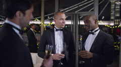 Stock Video Footage of 4K Male friends or business colleagues drinking &chatting at formal social event