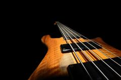 bass guitar strings with wooden close up black background - stock photo