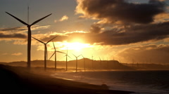 Wind turbine power generators silhouettes at stormy ocean coastline at sunset - stock footage