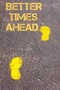 Yellow footsteps on sidewalk towards Better Times Ahead message - stock photo