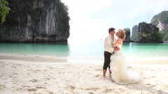 bride and groom kiss on beac - stock footage