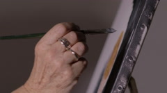 Woman painting: making particular on canvas with brush Stock Footage