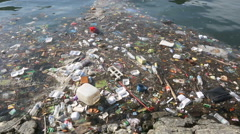 Plastic bottles and other trash floating in ocean - stock footage