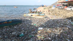 Waterfront scene of people in taxi boats in an ocean full of plastic garbage - stock footage