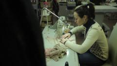 The girl seamstress works with the sewing machine at the factory Stock Footage