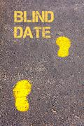 Yellow footsteps on sidewalk towards Blind Date message.Conceptual image - stock photo
