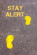 Yellow footsteps on sidewalk towards Stay Alert message.Conceptual image Stock Photos