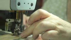 Stock Video Footage of The sewing machine is in operation. Closeup. Tailoring, аpparel manufacturing