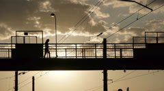 Silhouettes of people crossing the railroad on old metal bridge Stock Footage