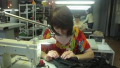 Stock Video Footage of Woman seamstress working at the factory. Tailoring, аpparel manufacturing