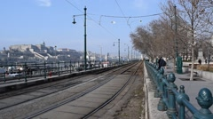View Down a Tram Track in Budapest. A Tram Comes to a Stop & Buda Castle Stock Footage