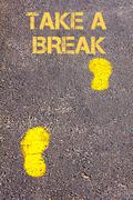 Yellow footsteps on sidewalk towards Take a break message.Conceptual image Stock Photos