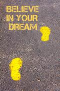 Yellow footsteps on sidewalk towards Believe in your dream message - stock photo
