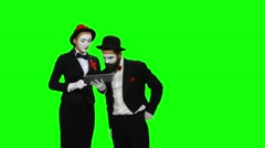 Two mimes watches something using tablet computer on green screen Stock Footage