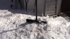 Shovels in a snowbank on sunny day Stock Footage