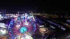 Aerial view of a carnival with rides and neon lights - stock footage