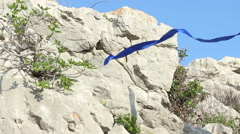 Blue ribbon and rock Stock Footage