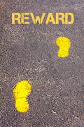 Yellow footsteps on sidewalk towards Reward message.Conceptual image Stock Photos