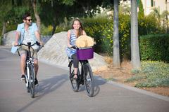 People riding rental or hire bikes Stock Photos