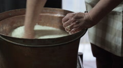 Woman cutting curdling with hand in a copper pot. Stock Footage