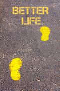 Yellow footsteps on sidewalk towards Better Life message.Conceptual image Stock Photos