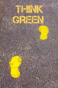 Yellow footsteps on sidewalk towards Think Green message.Conceptual image. Stock Photos