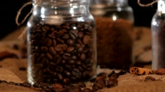 Roasted coffee beans in bottle on sacking, cam moves upwards Stock Footage