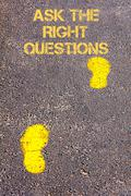 Yellow footsteps on sidewalk towards Ask The Right Questions message - stock photo