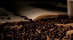 Coffee beans and music on sacking, black background Stock Footage