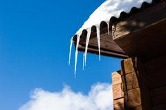 beautiful icicles glint in the sun against the blue sky - stock photo
