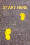 Yellow footsteps on sidewalk towards Start Here message.Concept image Stock Photos