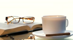 Delicious coffee and book with glasses, cinnamon, beans on white background Stock Footage